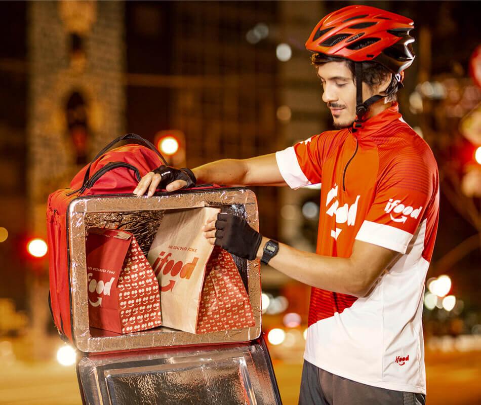 Entregador iFood arrumando os pedidos na bag